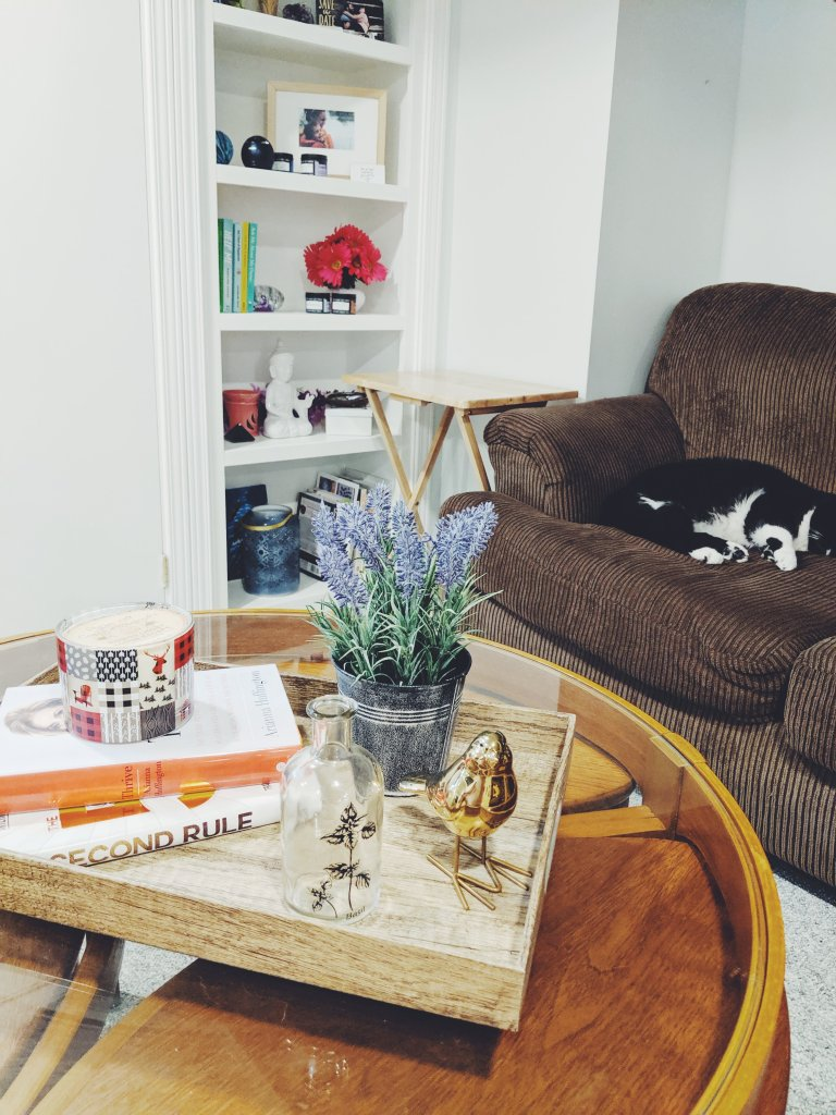 A photograph of coffee table styled with a faux wood tray and objects