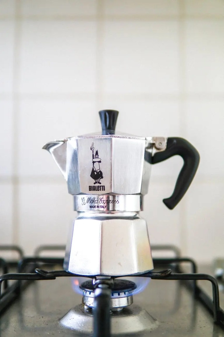 retro geyser coffee maker placed on gas stove
