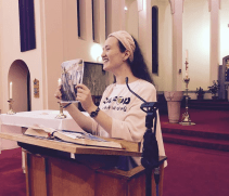 Sophie speaking at front of church