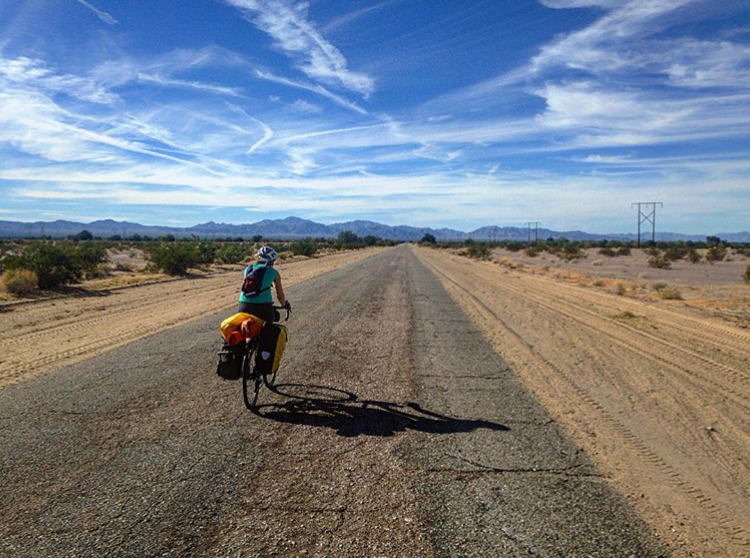A woman cycles through the desert with mountains in front of her.