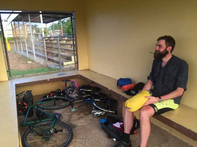 Bikepacker packing up after a sleep in a soccer hut during a bikepacking trip in Puerto Rico