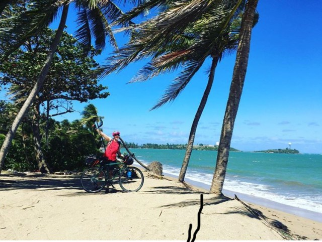 A cyclist stops near the ocean shore to take a picture while bikepacking Puerto Rico.