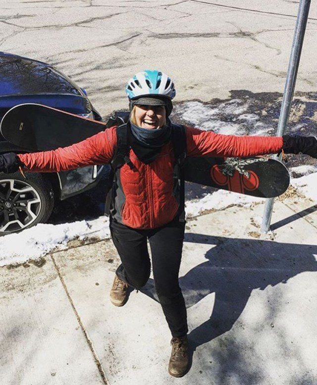 A woman carries a snowboard in her biking pack.