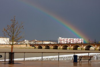 Rainbow over Garonne River and Pont de Pierre bridge