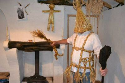 Man in straw outfit holding a Cailleach doll, another can be seen in the background wheat weaving straw craft