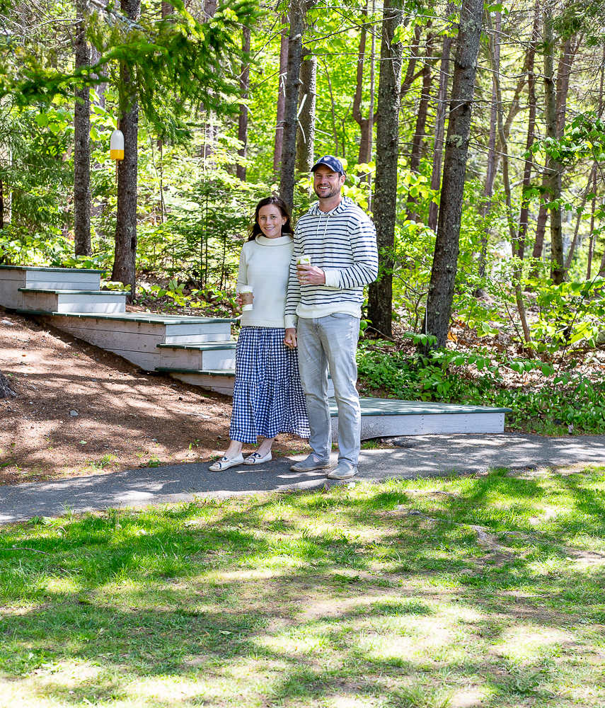 couple walking with coffee in the woods