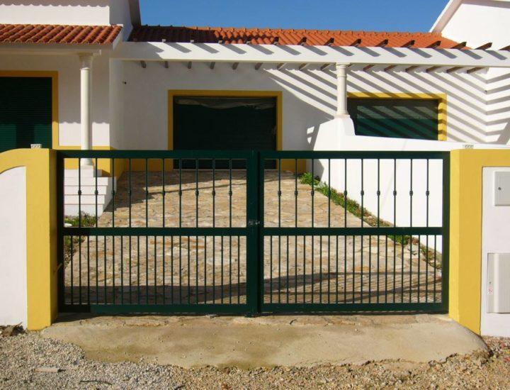 Moradia com caixilharia, gradeamento e portão basculante