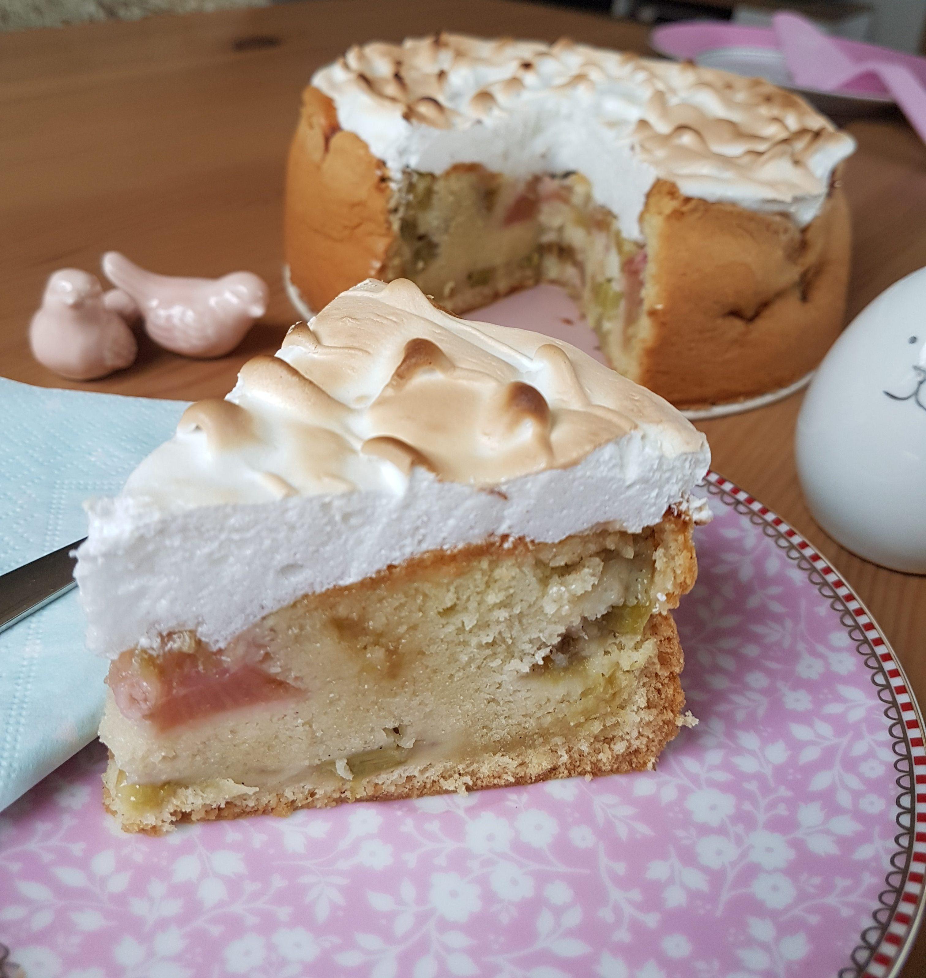 Rhabarberkuchen mit Baiserhaube von Cake Confession. Im Vordergrund sieht man ein Kuchenstück und dahinter ist der Kuchen mit Anschnitt zu sehen.