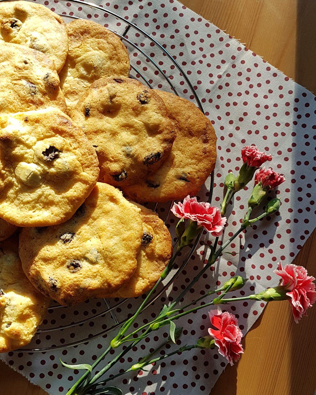 Cranberry-Weiße Schokolade-Cookies auf einem Kuchengitter mit Nelkenblüten bei Sonnenlicht