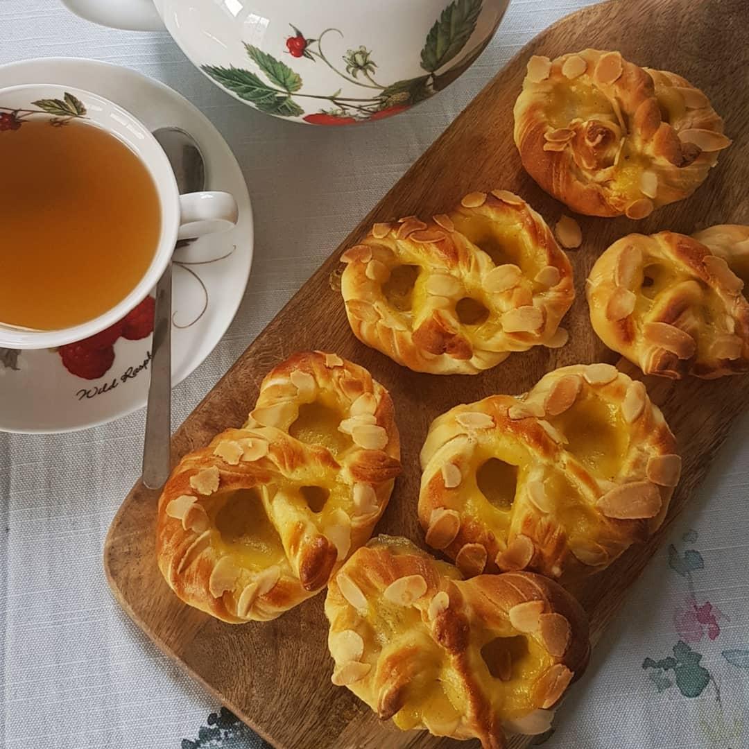 Vanille Puddingbrezeln von Cake Confession auf einem Holzbrett. Daneben sieht man eine Teetasse und Kanne.