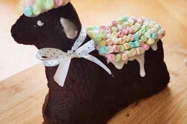 Dunkles Schokoladen-Osterlamm von Cake Confession mit Marshmellow-Fell in Pastellfarben.