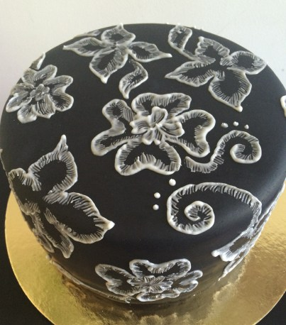 Chocolate strawberry cake with black fondant and white icing flowers