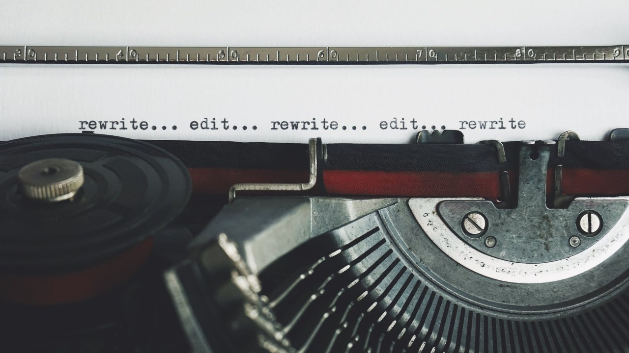Close up of a typewriter ribbon and letter keys plus typed words on a sheet of paper saying rewrite, edit, rewrite, edit, rewrite.