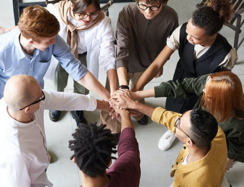 people putting hands together in a circle