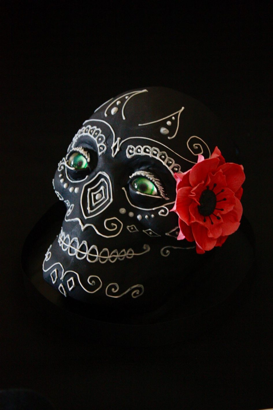 black and white sugar skull cake with pink flower.