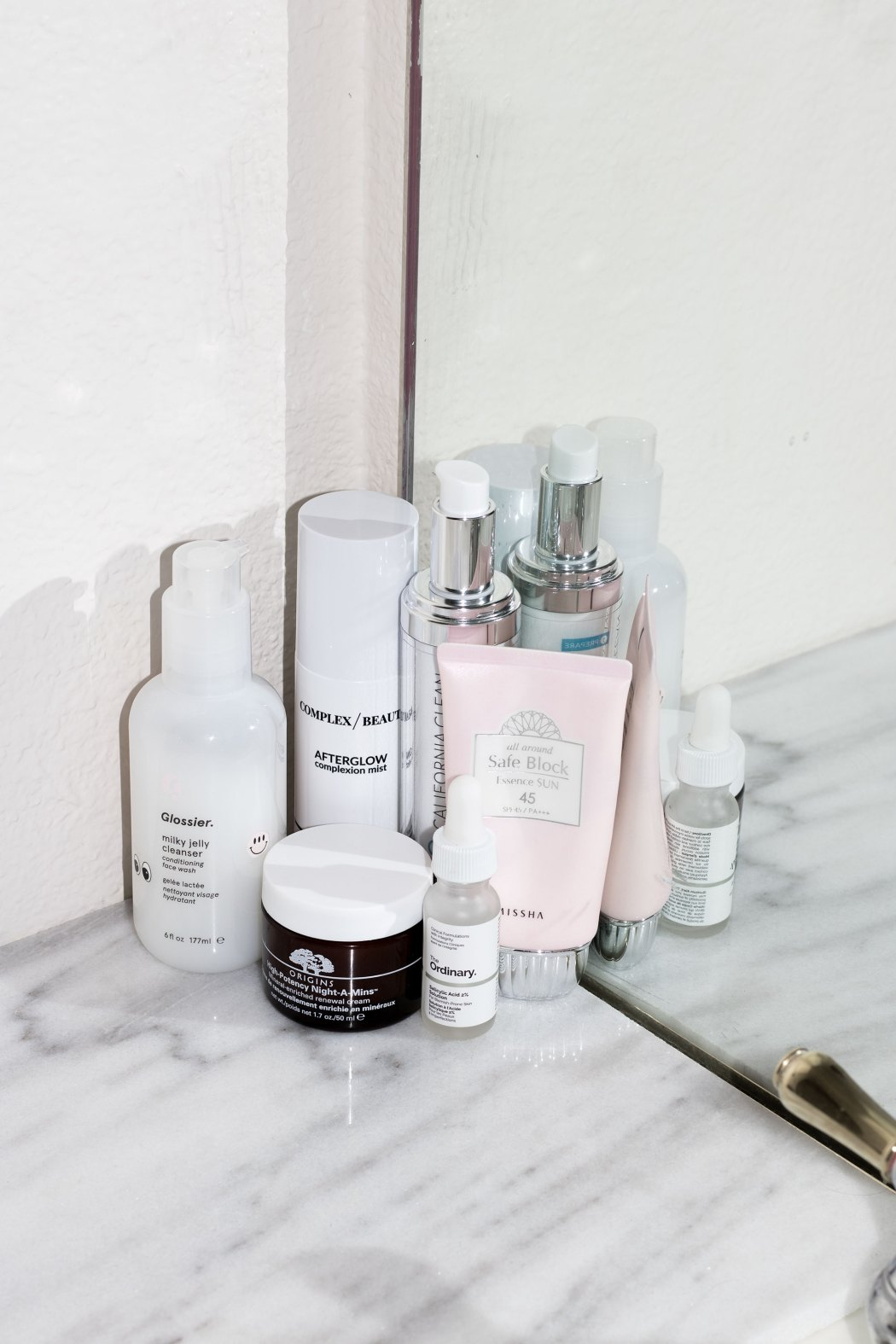 Travel beauty essentials Glossier Milky Jelly cleanser, burberry fresh glow base nude radiance, missha spf pink tube, origins night a mins, skincare, becca opal, butter london eye glaze, glossier cloud paint dusk