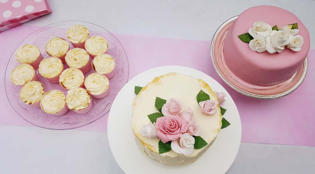 Det färdiga dessertbordet vid examensfesten – citroncupcakes med citronfrosting, chokladbollstårta med smörkräm, och en traditionell tårta med jordgubbsmousse och vaniljmousse, täckt med vit chokladsmörkräm och marsipan.
