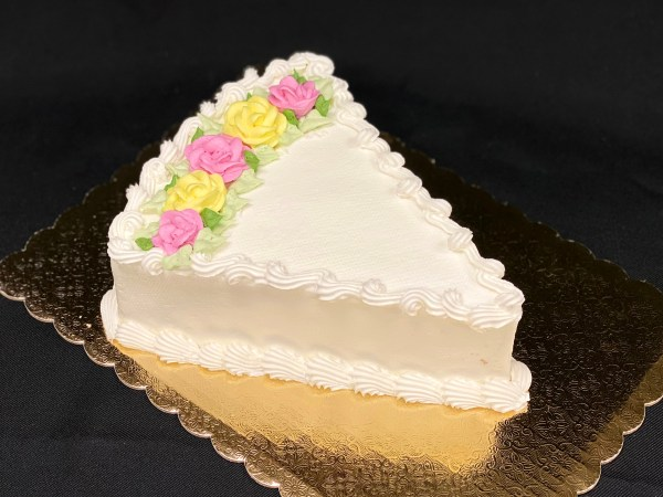 Wedge shaped frosted cake with flowers