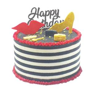 A black and white cake with a cutout of golden heels and a red lip with a happy birthday topper