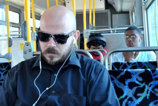 "Cody Miller (foreground) relies on the GET bus as his only form of transportation to get to and from work, and often finds it constraining. ""I could work more hours if the buses ran later,"" says Miller. Kevin Martin (right) says he ""only rides the bus a couple times a month"" when he ""needs to go somewhere."""
