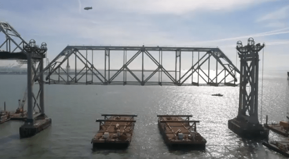 A blimp, a bridge, and waiting barges. Image: screengrab from Caltrans' live webcast of Bay Bridge takedown