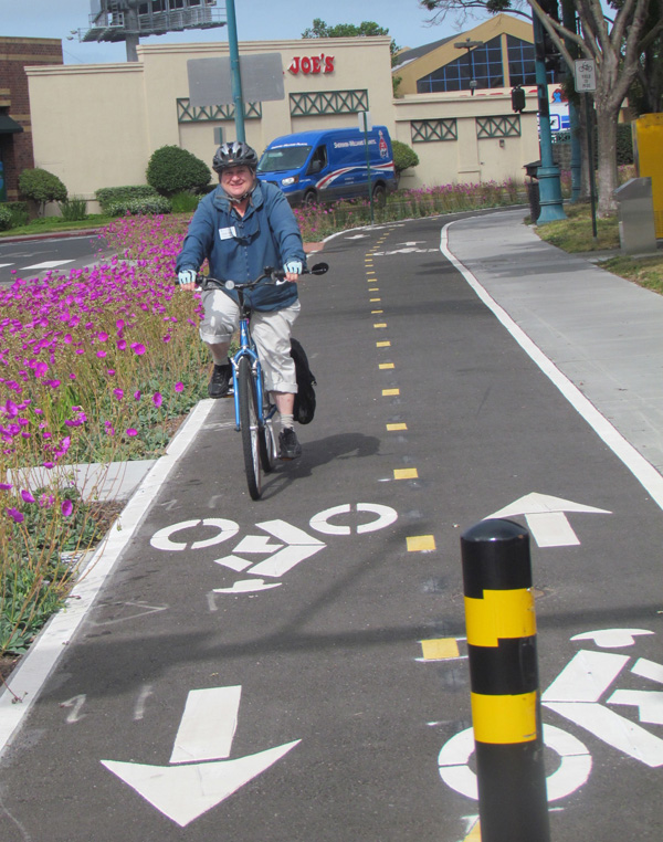Councilmember Ruth Atkins takes a spin on the new, beautifully landscape-protected, two-way cycletrack. Photo: Melanie Curry/Streetsblog