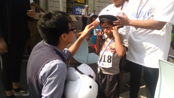 City of Santa Ana staff and volunteers give out helmets to passersby. Photo by Kristopher Fortin.
