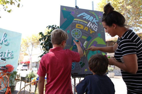 Krystin Gibson, 30, and her sons Nolan, 4, and Lynk, 7, draw on a community painting board at Orange County's Parking Day on September 17 in downtown Garden Grove. Photo by Kristopher Fortin