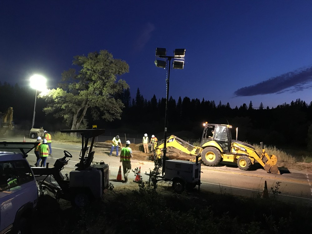 A photo of roadway workers repairing a section of a highway at night while a backhoe escavates material.