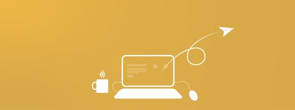 Tietokone jossa artikkeli auki, kahvikuppi sekä paperilennokki ja hiiri