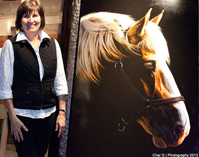 "- Halvorson, poses with her painting ""Pulling Together"", which sold for $125,000 at auction on July 11, 2013. The painting took her more than two months to finish."
