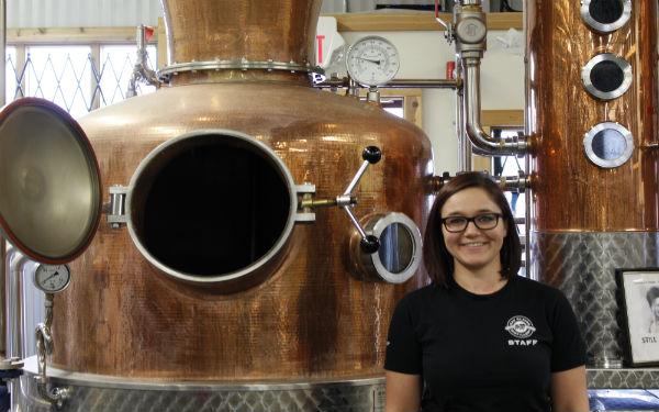 Caitlin Quinn standing near distilling equipment
