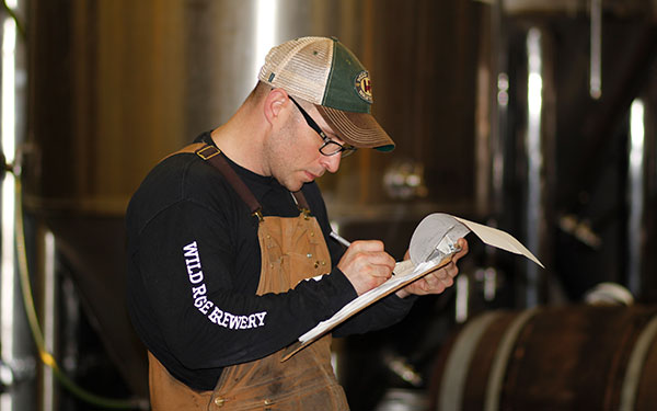 Kerrigan checks off an order list of the taproom's specialty brews for Wild Rose. Photo by Noel Harper.