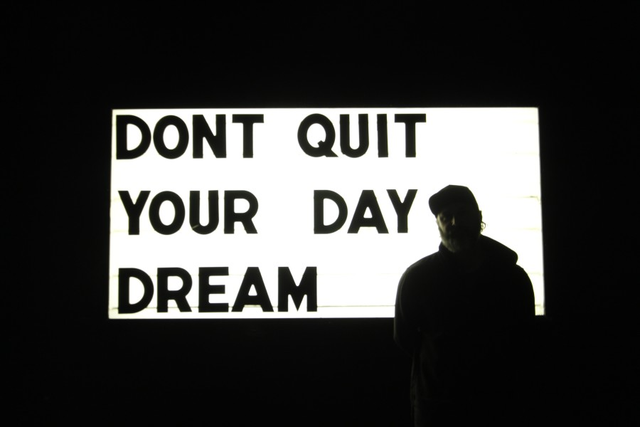 """Late Saturday night, at the front entrance of the NVRLND building, Nespor stands proudly in front of one of his projects, """"Don't quit your day dream"""". Photo by Sarah Akeredolu."""