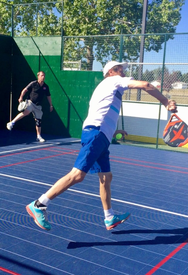 Player smashing the ball at the net during a padel match