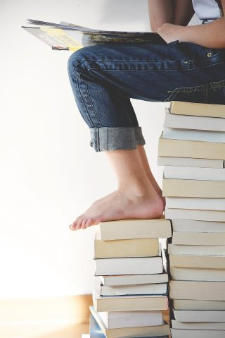 Photo of lady reading while sitting on a stack of books