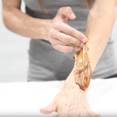 Woman using sugar paste for arm hair removal