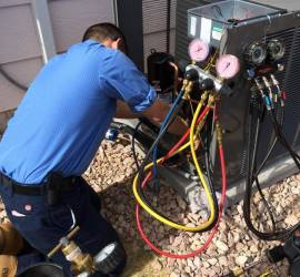 Service technician working on an Air Conditioning Condenser - air conditioner is not working properly