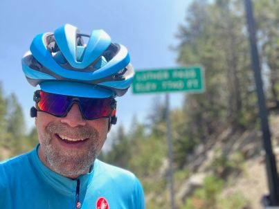 Mark smiling while standing in front of the Luther Pass sign. During his ride on August 2, 2020.