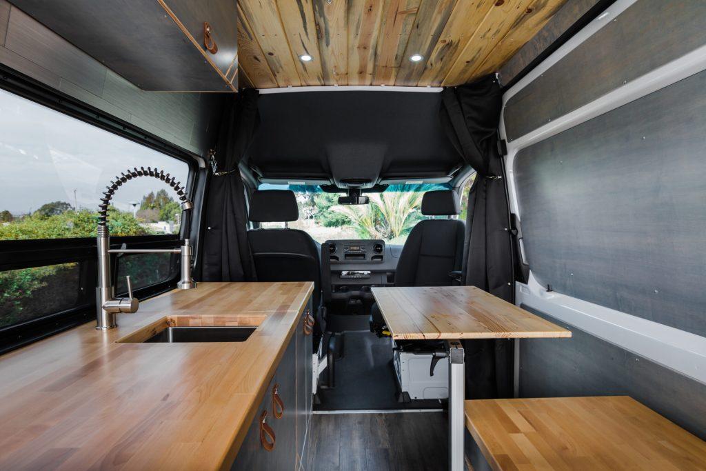 Custom camper van kitchen with butcher block countertops, Lagun table and swivel seat.