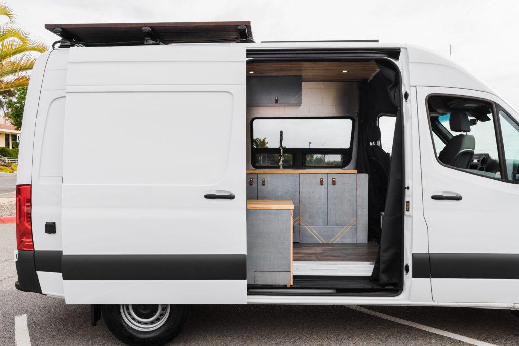 Mercedes Sprinter custom camper van with kitchen, refrigerator and roof deck.