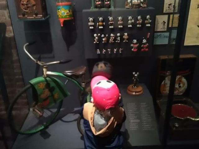 A young visitor admires vintage Mickey Mouse paraphernalia at the Walt Disney Family Museum in San Francisco