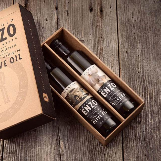 An open box containing two bottles of olive oil from Enzo Olive Oil Co., one of the gourmet gift ideas from California News Press' 2020 Holiday Gift Guide