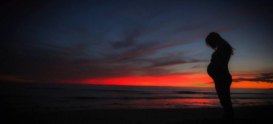 Femme enceinte, maternité au coucher de soleil sur la plage