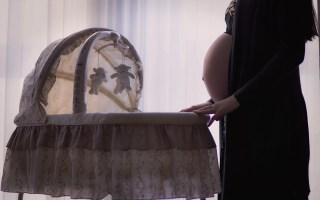 Femme enceinte préparant l'arrivée de son bébé, on y voit un berceau et des petits jouets d'enfant.