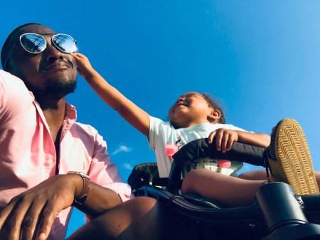 papa et enfant jouant dans une poussette