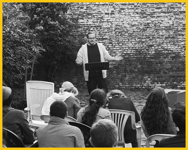 Un orateur lit un texte devant son public, dans le jardin.