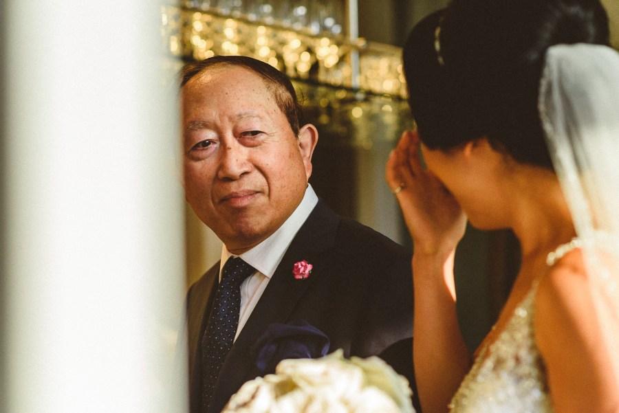 Dad of bride looking at crying bride