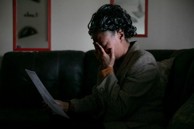 Kello Gordon se derrumba mientras mira una foto de su hijo, David Lee Williams, en su casa de Sacramento. Dijo que Williams está enfermo de COVID-19 en la cárcel del condado de Sacramento y le preocupa que no esté recibiendo la atención médica que necesita mientras espera su juicio. Foto de Anne Wernikoff, CalMatters