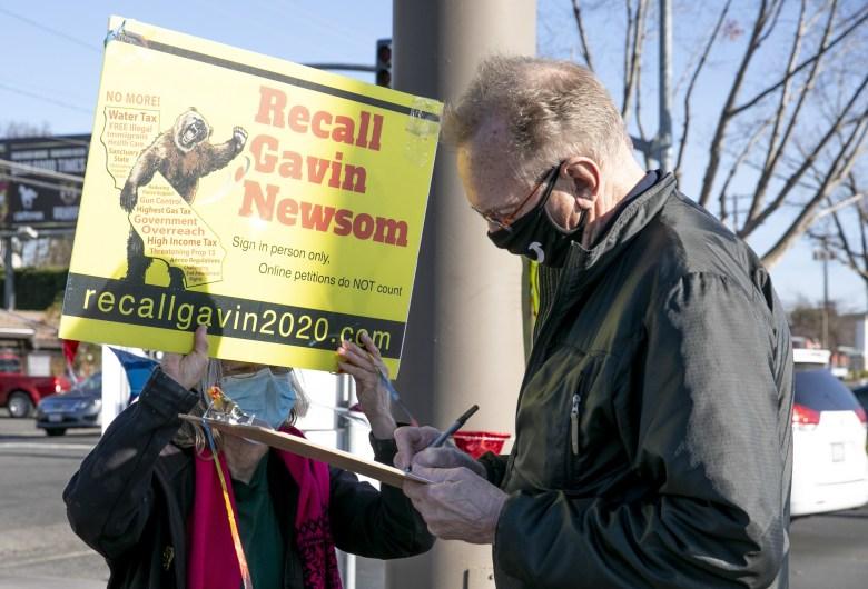"""Un voluntario observa cómo Bob Bickers, residente de Sacramento, firma la petición para destituir al gobernador Newsom el 5 de enero de 2021. Bickers, quien dice que no votó por Newsom en 2018, le gustaría que lo retiraran debido al actual 'estado de asuntos."""" Foto de Anne Wernikoff, CalMatters"""